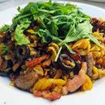 Gotowe danie - bezglutenowy makaron z pieczarkami i boczkiem razem z rukolą